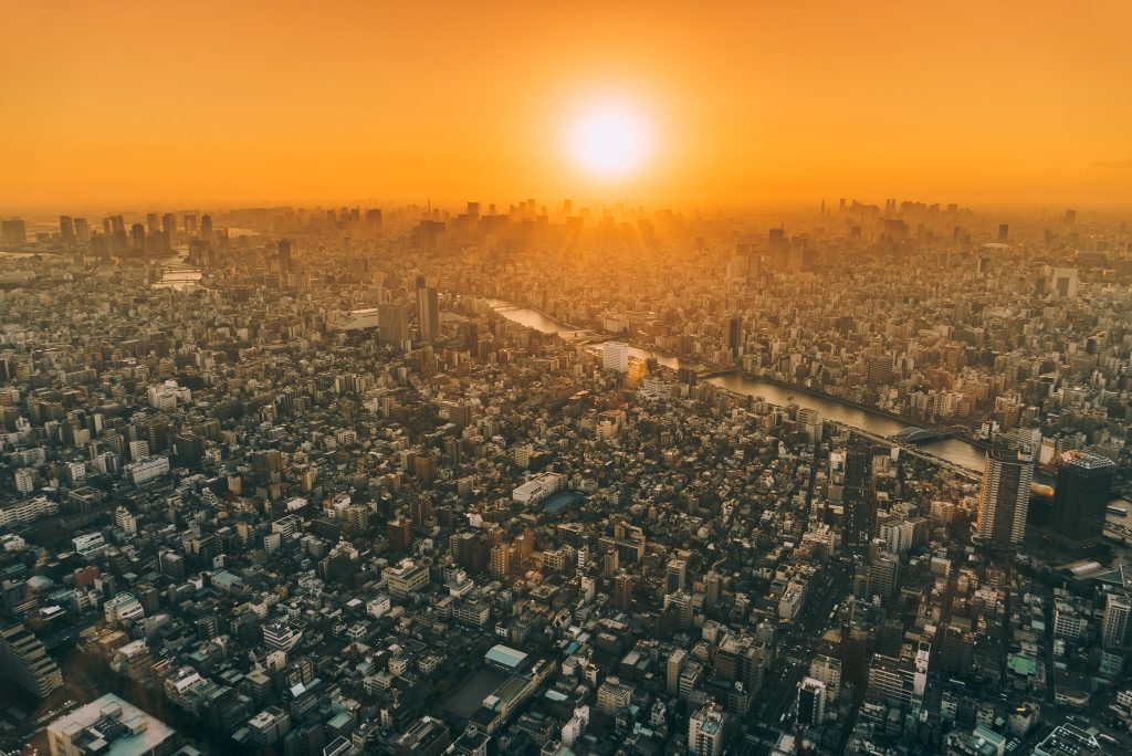 orange smoggy sunset over a never ending city
